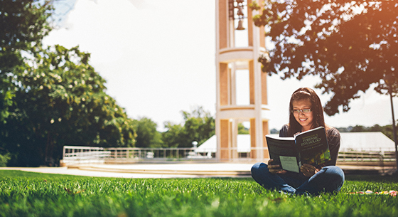 Photo of Hispanic girl reading a book on the bell tower quad